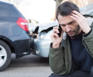 Man on phone after car accident.